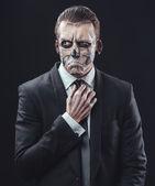 Pensive businessman with makeup skeleton — Photo