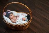 Newborn baby in  cap  basket on  floor — Stock Photo
