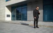 Zakenman op zoek naar telefoon in de buurt van office — Stockfoto