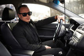 Man in  black suit sitting behind the wheel — ストック写真