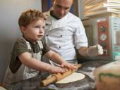 Little boy rolls pizza dough — Stock Photo