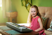 Cheerful girl sits near an  piano — Stock Photo