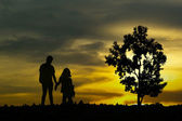 View of young couple walking along the shore during sunset — Stock Photo