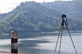 Camera with tripod over sun rising near the lake — Stock Photo