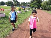 Escolares caminando a la escuela en camino bajo la luz del sol — Foto de Stock