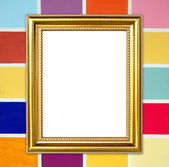 Golden frame on colorful wood wall background — Stock Photo