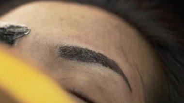 Makeup eyebrow tattooing, pretty asian woman face closeup — Stock Video