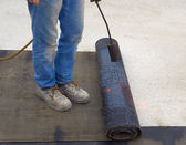 Worker preparing part of bitumen roofing felt roll for melting by gas heater torch flame — Stock Photo