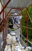 Bezpieczeństwo w pracy. Pracownik montuje rusztowania — Zdjęcie stockowe