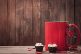 Red mug with coffee and chocolates on Valentine's Day — Стоковое фото