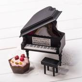 Candy and miniature grand piano on a paper napkin — Stock Photo