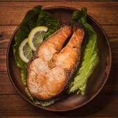 Baked trout steak in pottery with salad and slices of lemon, top view — Stock Photo