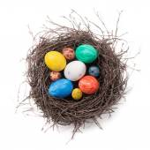 Colorful Easter eggs in a nest on a white background. Top view — Stock Photo