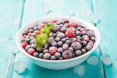 Plate of fresh frozen berries on a turquoise background, closeup — Stock Photo