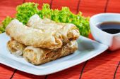 Fried spring rolls on red bamboo mat — 图库照片