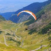Lago balea, rumanía - 21 de julio de 2014: parapente no identificada en el lago balea, montañas de fagaras, rumanía. parapente es uno de los más populares deportes de aventura en el mundo — Foto de Stock