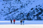 Morskie Oko Lake, POLAND - MARCH 14: Unidentified group of tourists are walking on the frozen Morskie Oko Lake, Poland on March 14, 2014.Tatra Mountains is very popular travel destination. — Stock Photo