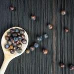 Juniper berries on old wooden spoon — Stock Photo #69766089