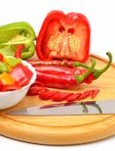 Sweet pepper, chili pepper on the board with a knife  — Stock Photo