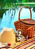 Cowboy hat, wicker basket,  spool andfishing tackle in the nature — Stock Photo