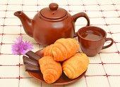 коричневый чайник, sauser с круассаном и кубок — Стоковое фото