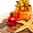Starfish, christmas ball, gift boxes on the sand — Stok fotoğraf #57637025