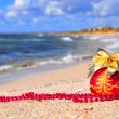 Red christmas ball with golden bow on the sand — Stock Photo #57637083