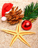 Starfish, christmas baubles and pine twig on the sand — Foto Stock