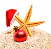 Starfish, christmas buable and Santa Claus hat on the sand — Stock Photo