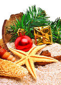 Christmas baubles, starfish, gift box and pine twig on the sand — Stock Photo