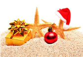 Starfishes, christmas bauble and a gift box on the sand — Stock Photo