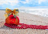 Red christmas bauble with golden bow on the sand — Stock Photo