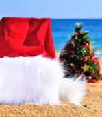 Christmas hat and blurred christmas tree on the seashore — Stock Photo