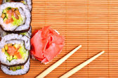 Sushi, rolls, ginger and chopstick on bamboo mat — Photo