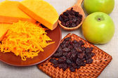 Ripe raw pumpkin with grated pumpkin, apples and heap of raisins — Stock Photo