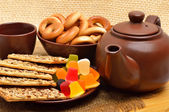 Ceramic teapot and cup with cookies, cracknels, jellies on the p — Stock Photo