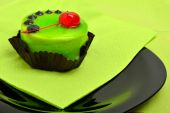 Delicious green cake with cherry on green napkin on black plate  — Stock Photo