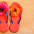 Red flip-flops, slippers with flowers on the wooden background — Stock Photo #63829807