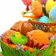Easter eggs in the basket, chocolate eggs and muffins on the gra — Stock Photo #67762493
