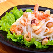 Rice noodles with seafood, olives and green salad on black plate — Stock Photo