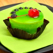 Delicious green cake with cherry on black plate on cutting backg — Stock Photo