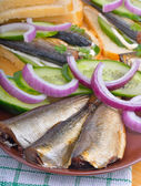 Sprats with green cucumber and onion — Stock Photo