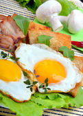 Bacon with sunny side up eggs served with toasts — Stock Photo