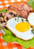 Bacon with sunny side up eggs served with toasts on a orange nap — Stock Photo