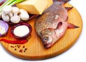 Baked fish with vegetables, sauce, red pepper on cutting board — Stock Photo