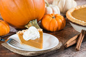 Slice of a pumpkin pie and pumpkins on the background — Stock Photo
