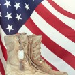 Old combat boots and dog tags with American flag — Stock Photo #72079701