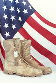 Old combat boots and dog tags with American flag — Stock Photo