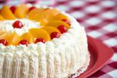 Homemade cream cake with peaches and cherries — Stock Photo