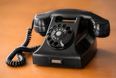 Old rotary dial phone on wooden desk — Stock Photo